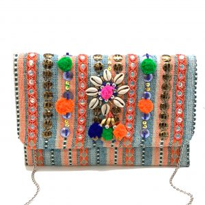 EMBELLISHED CLUTCH WITH COWRIE SHELLS AND MULTI-COLORED POMPOMS